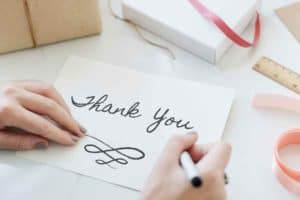 Thank you written on a blank card with pen in right hand