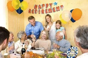 """a family celebrating at a retirement party. There is a banner on the wall that says """"happy retirement"""""""