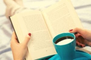 A person reading a book while holding a cup of coffee. The book is on their lap, and their legs are stretched out straight. The cup is resting on their belly.
